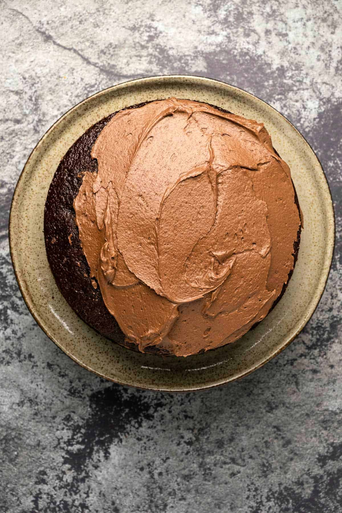 Chocolate buttercream frosting spread onto a chocolate cake.