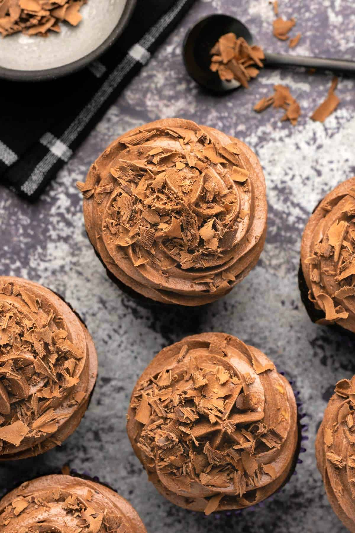 Chocolate cupcakes topped with chocolate buttercream and chocolate flakes.