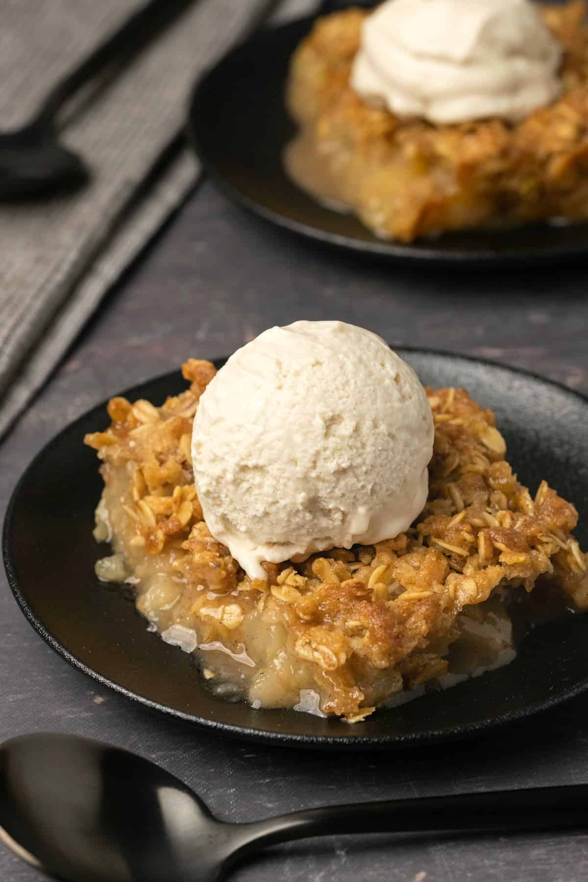 Slice of apple crisp topped with vanilla ice cream on a black plate.