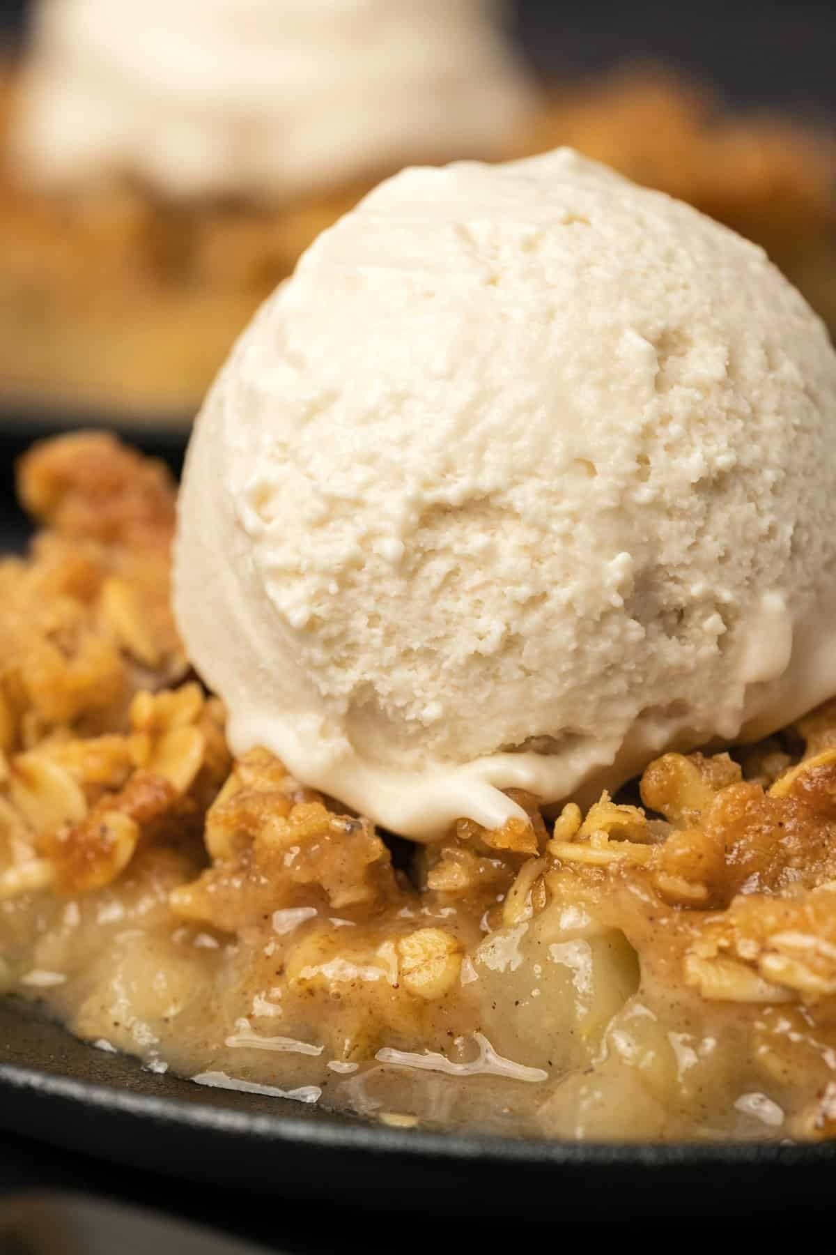 Slice of apple crisp topped with a scoop of vanilla ice cream.