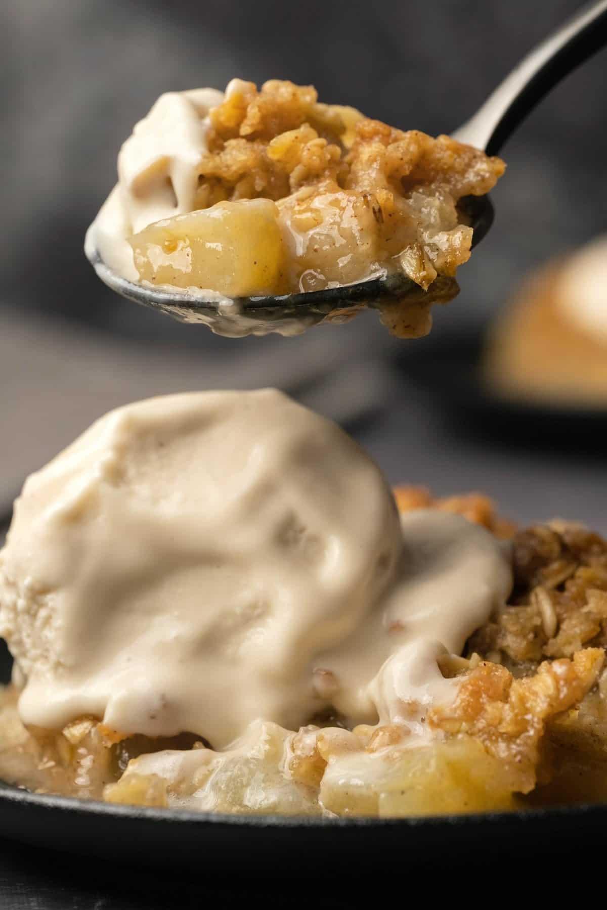 Spoonful of apple crisp with ice cream.