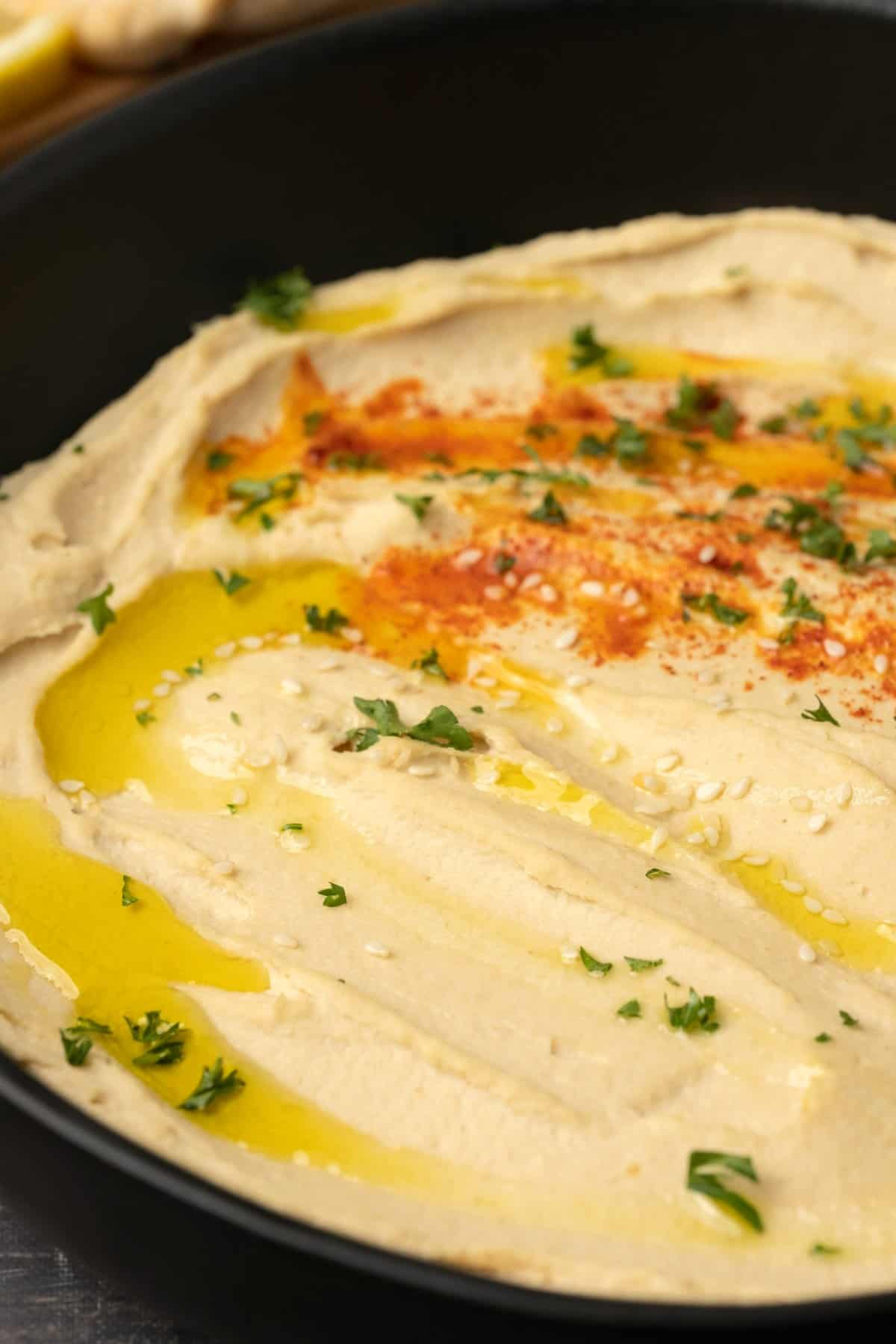 Hummus drizzled with olive oil in a black bowl.
