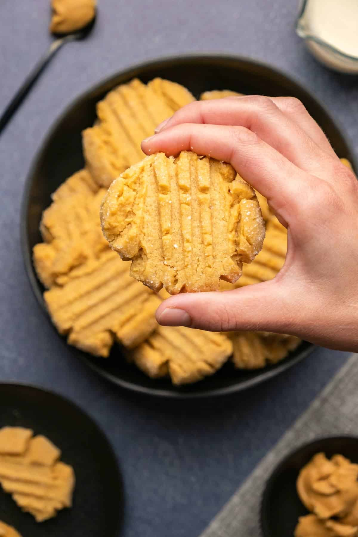 Holding a peanut butter cookie up above a bowl of cookies.