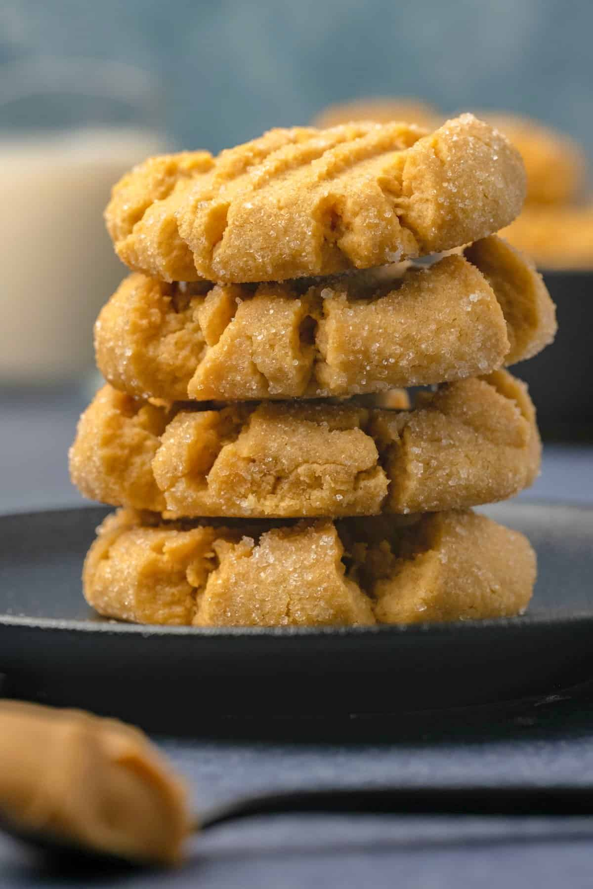 Peanut butter cookies stacked up on a black plate.