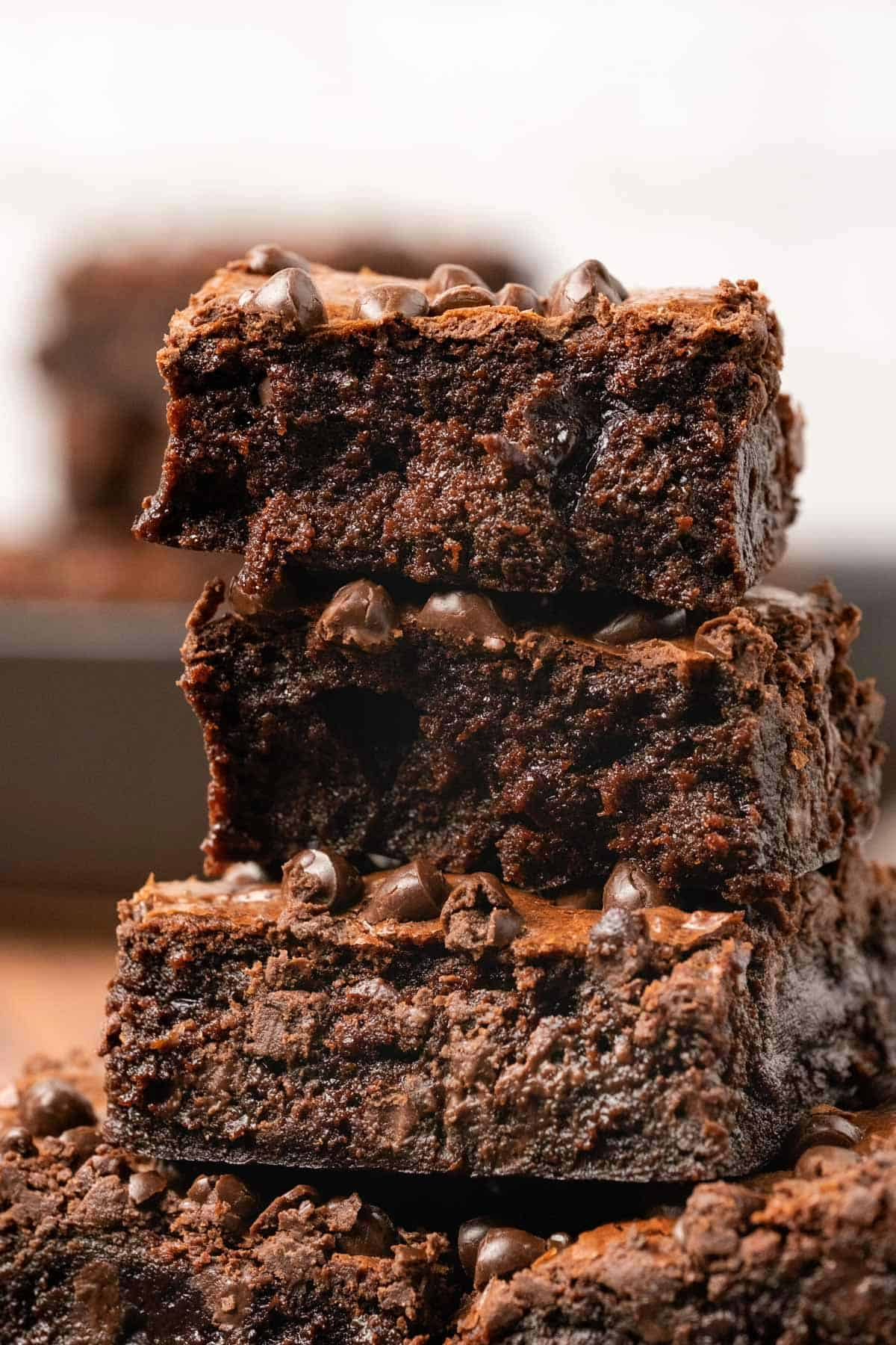 A stack of brownies on a plate with the top one broken in half.