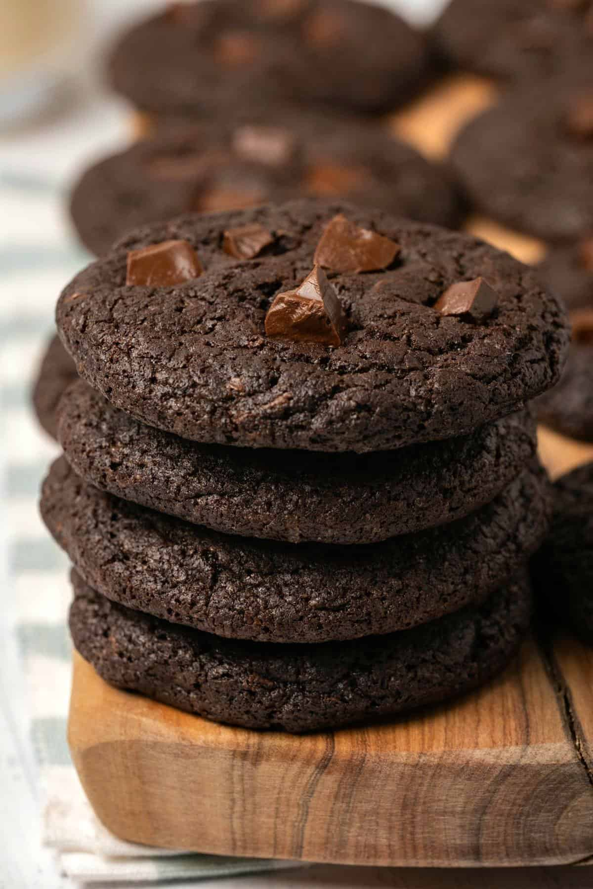 Chocolate cookies topped with chocolate chunks in a stack.