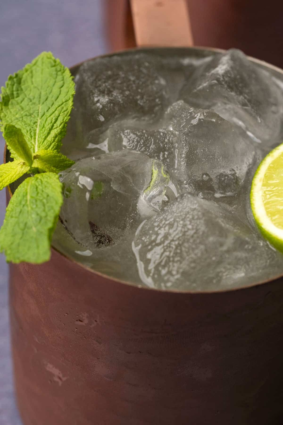 Moscow mule in a copper mug with a lime wedge and fresh mint.