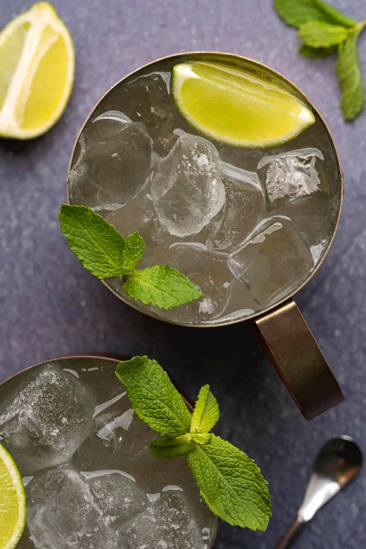 Moscow mule served in a copper mug with a wedge of lime and fresh mint leaves.