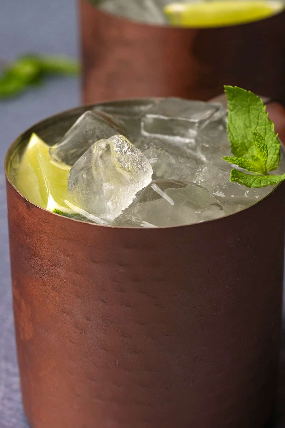 Moscow mule cocktail in a copper mug with fresh mint leaves and a lime wedge.