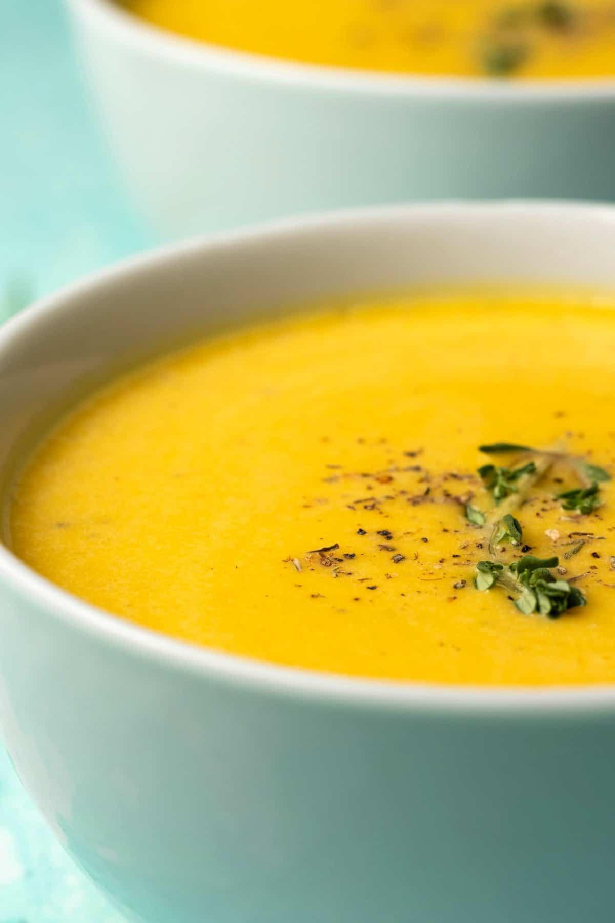 Pumpkin soup in a white bowl.