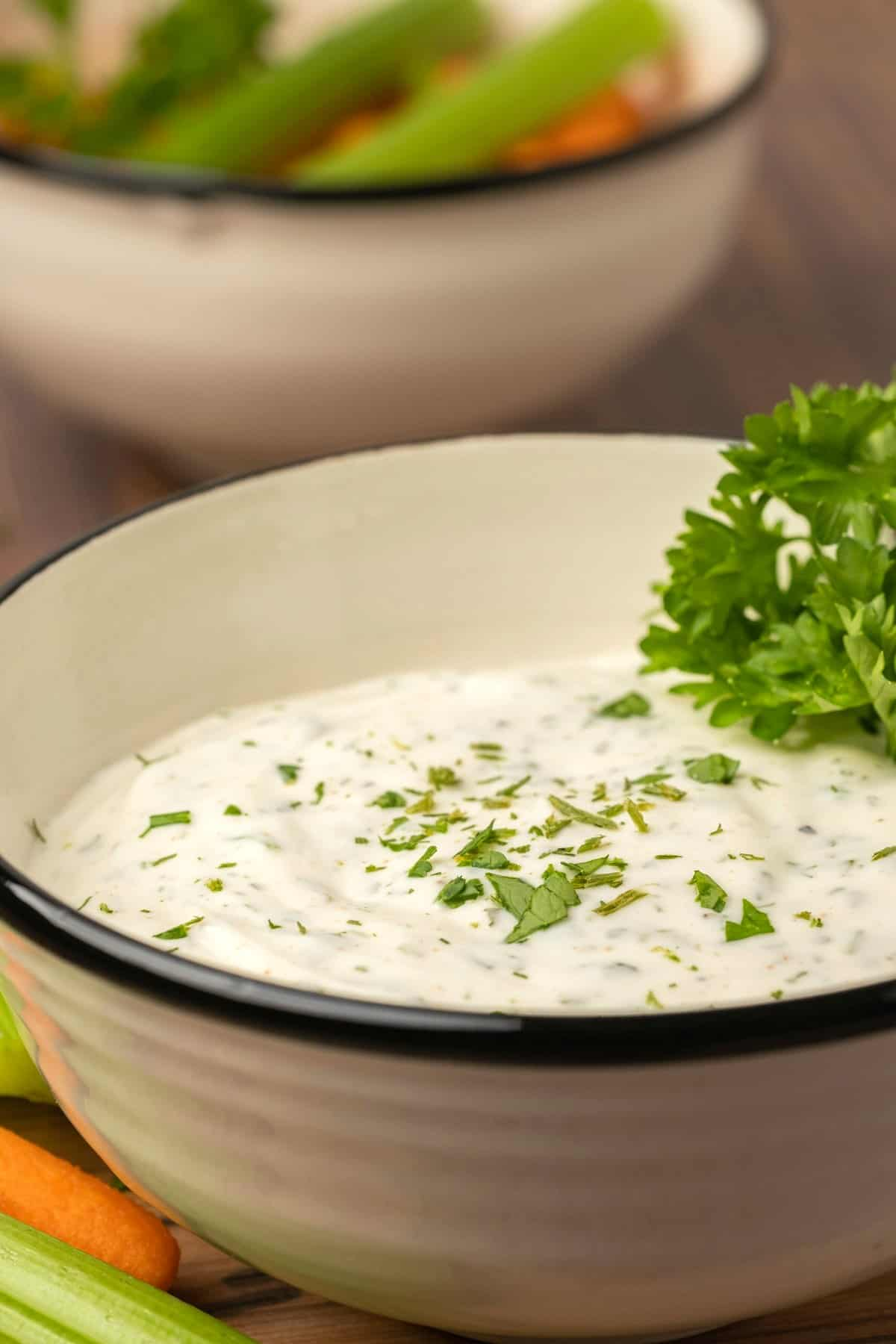 Ranch dressing topped with fresh parsley in a ceramic bowl.