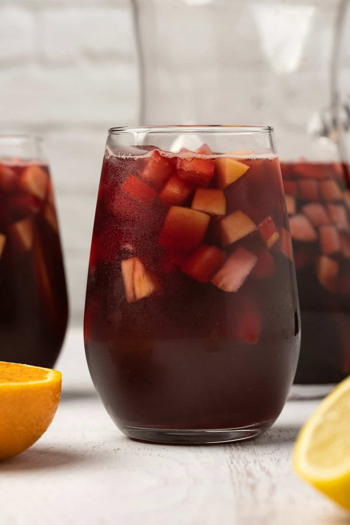 Sangria in a tall glass with ice and chopped fruit.