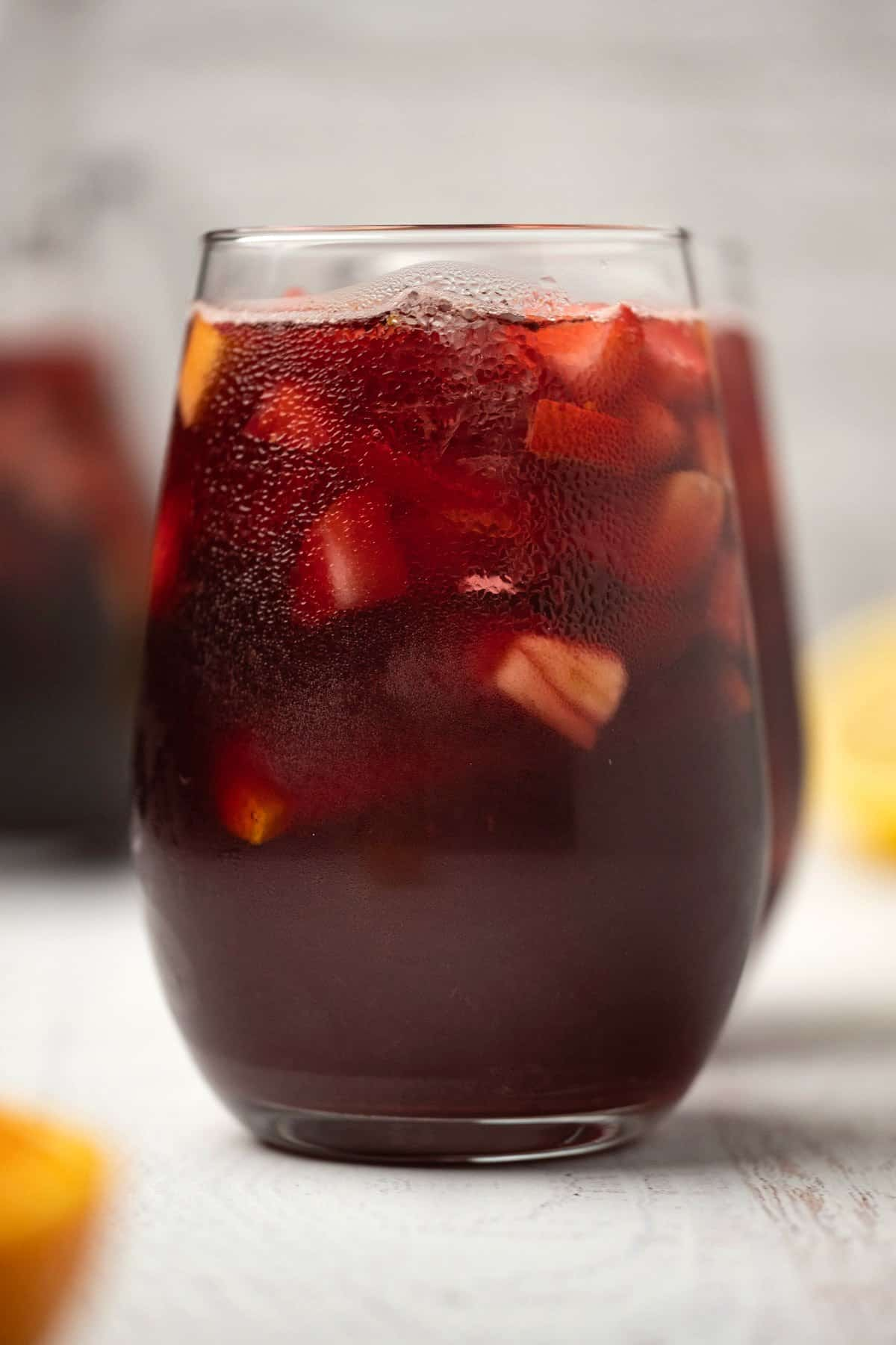 Sangria in a glass with ice and chopped fruit.