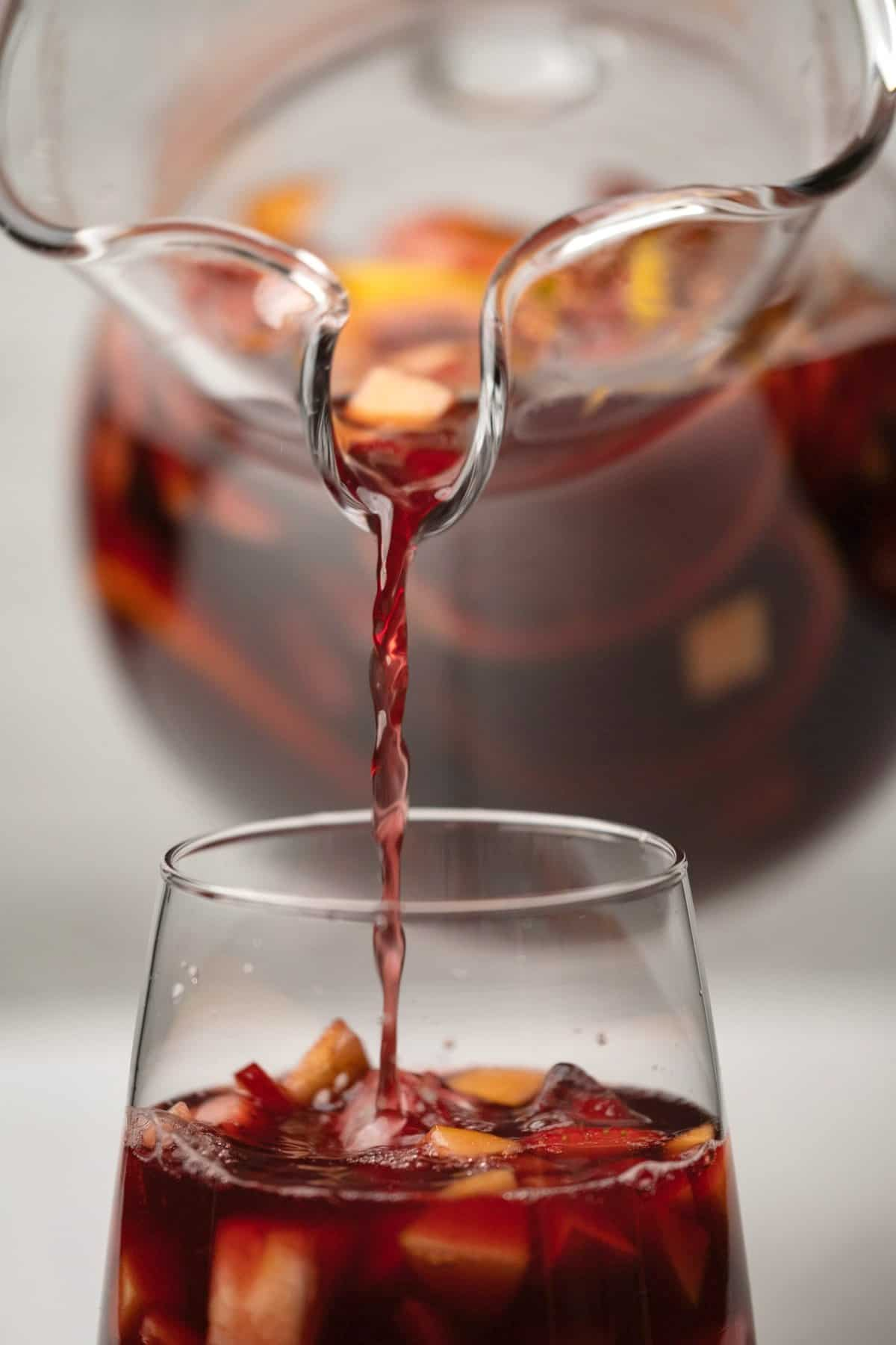 Sangria pouring from a jug into a glass with ice.