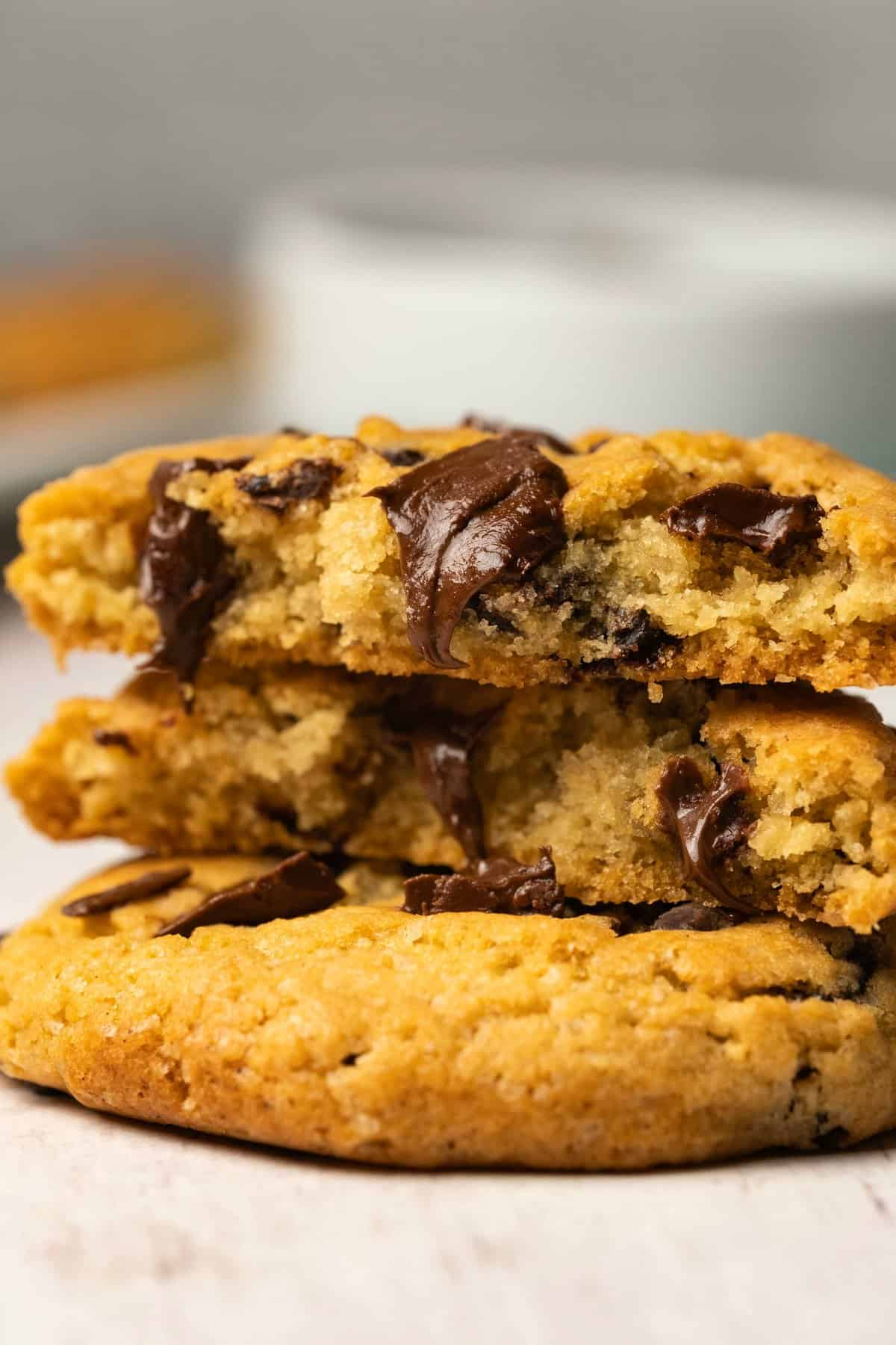 Chocolate chip cookies in a stack with the top cookie broken in half to show the center.