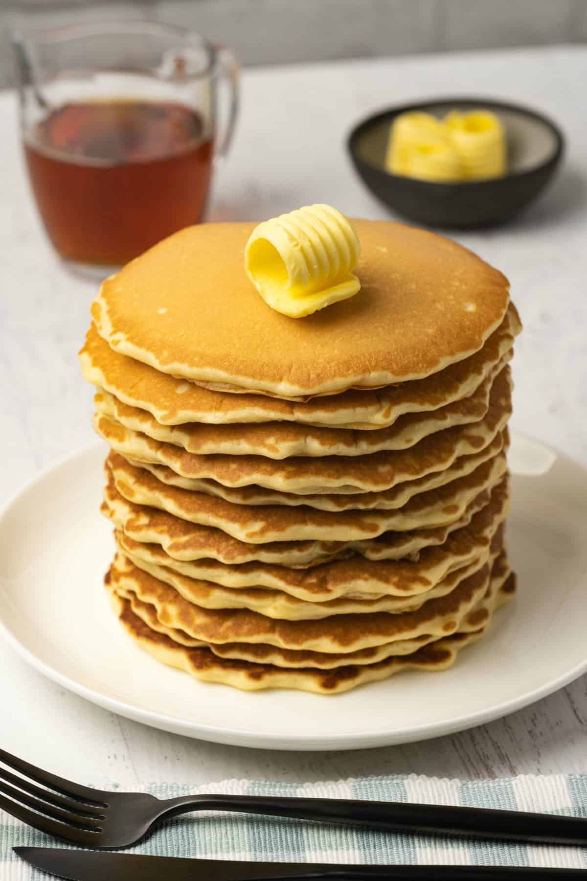 Stack of pancakes topped with a pat of butter on a white plate.