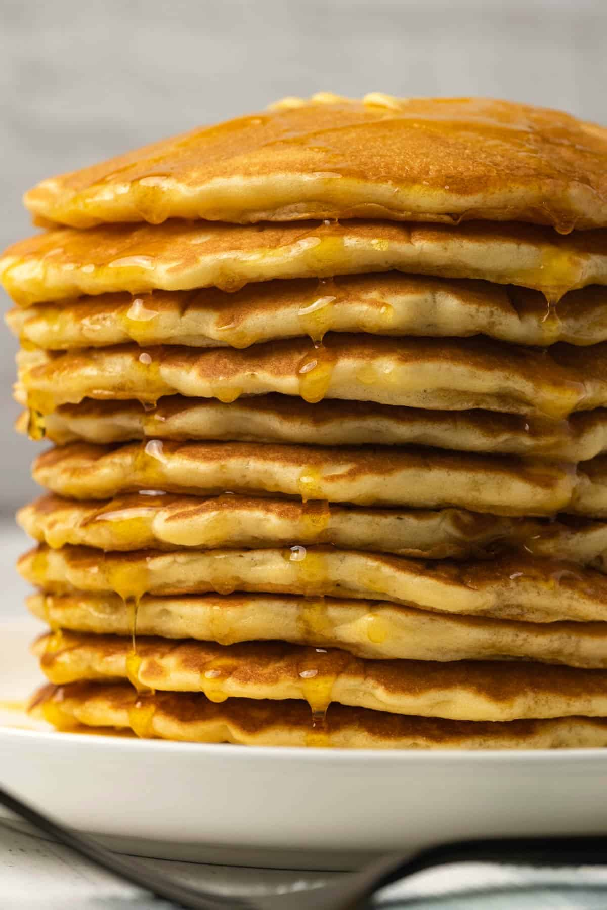 Stack of pancakes with butter and syrup on a white plate.
