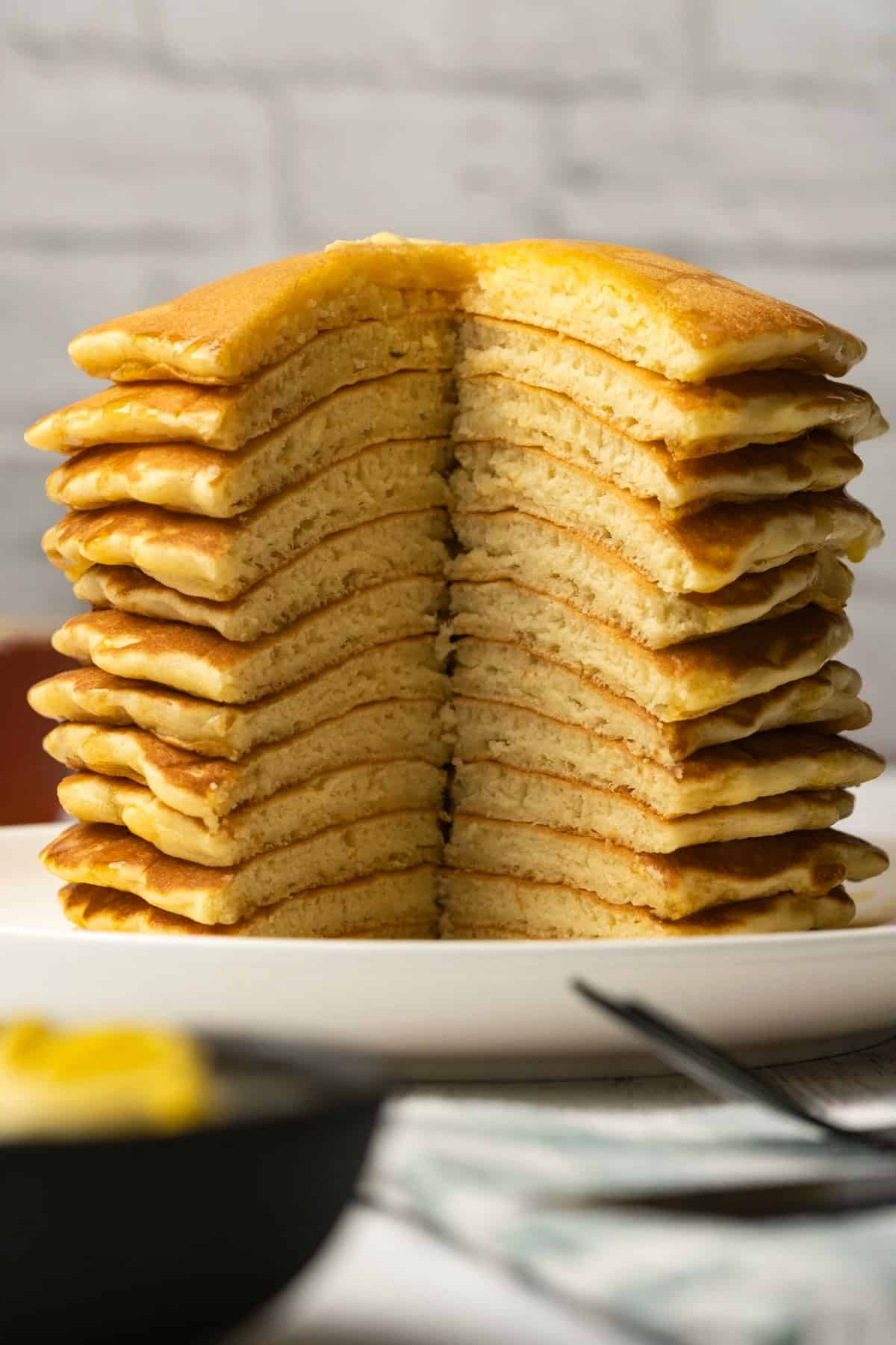 Stack of pancakes with a section cut out of the stack, on a white plate.