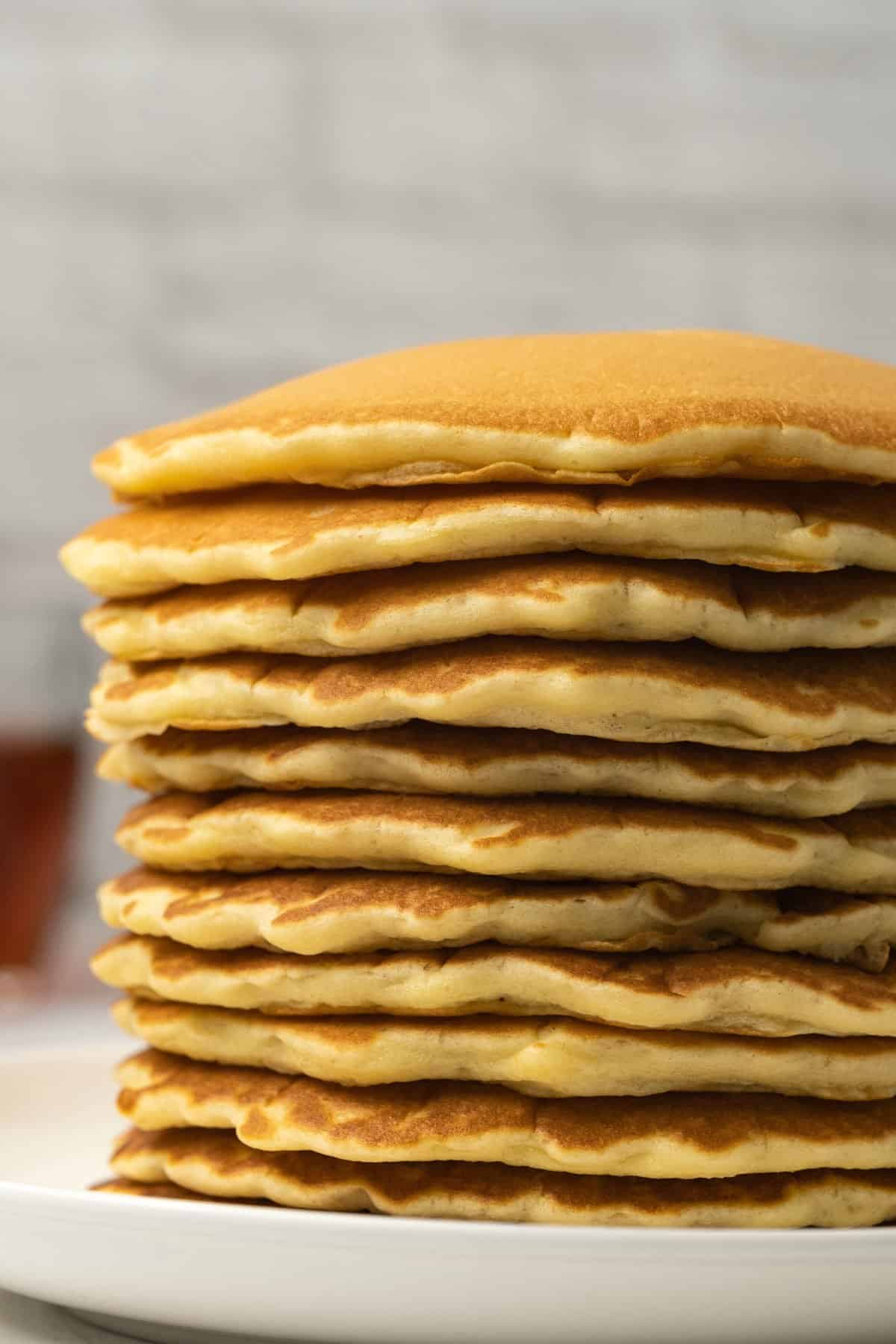 Stack of pancakes on a white plate.
