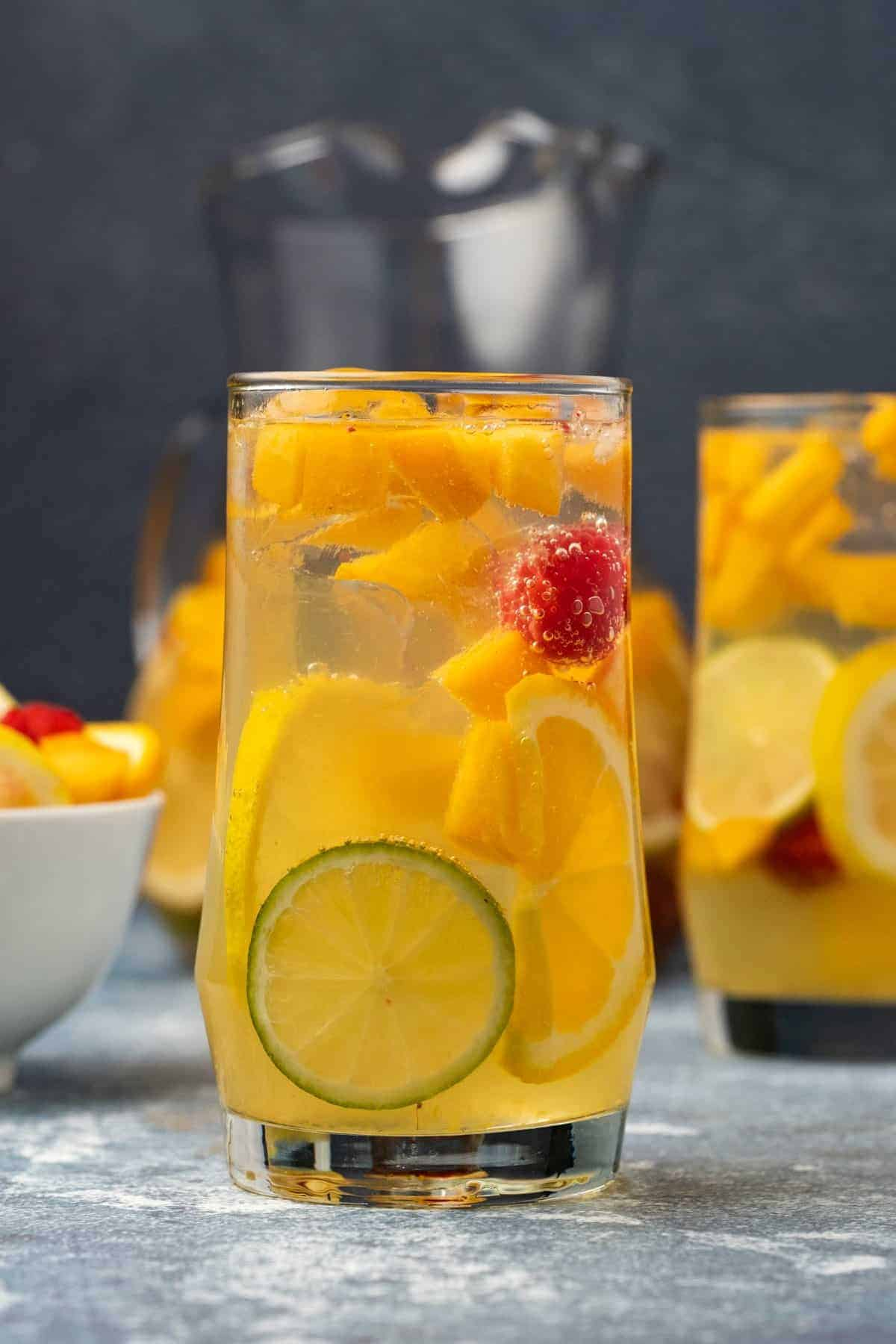 White sangria in a tall glass with fresh peaches, raspberries and citrus.