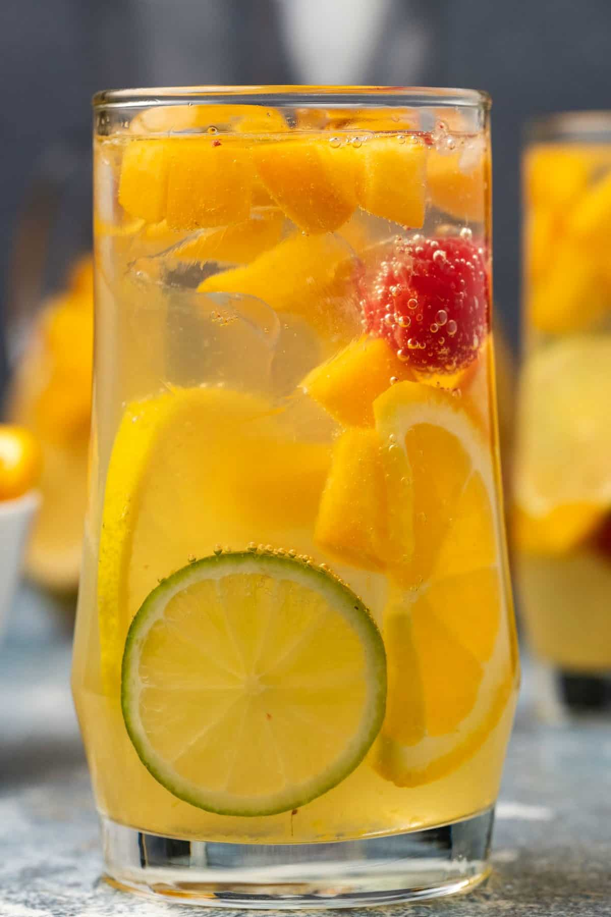 Tall glass filled with white sangria and fresh fruit.