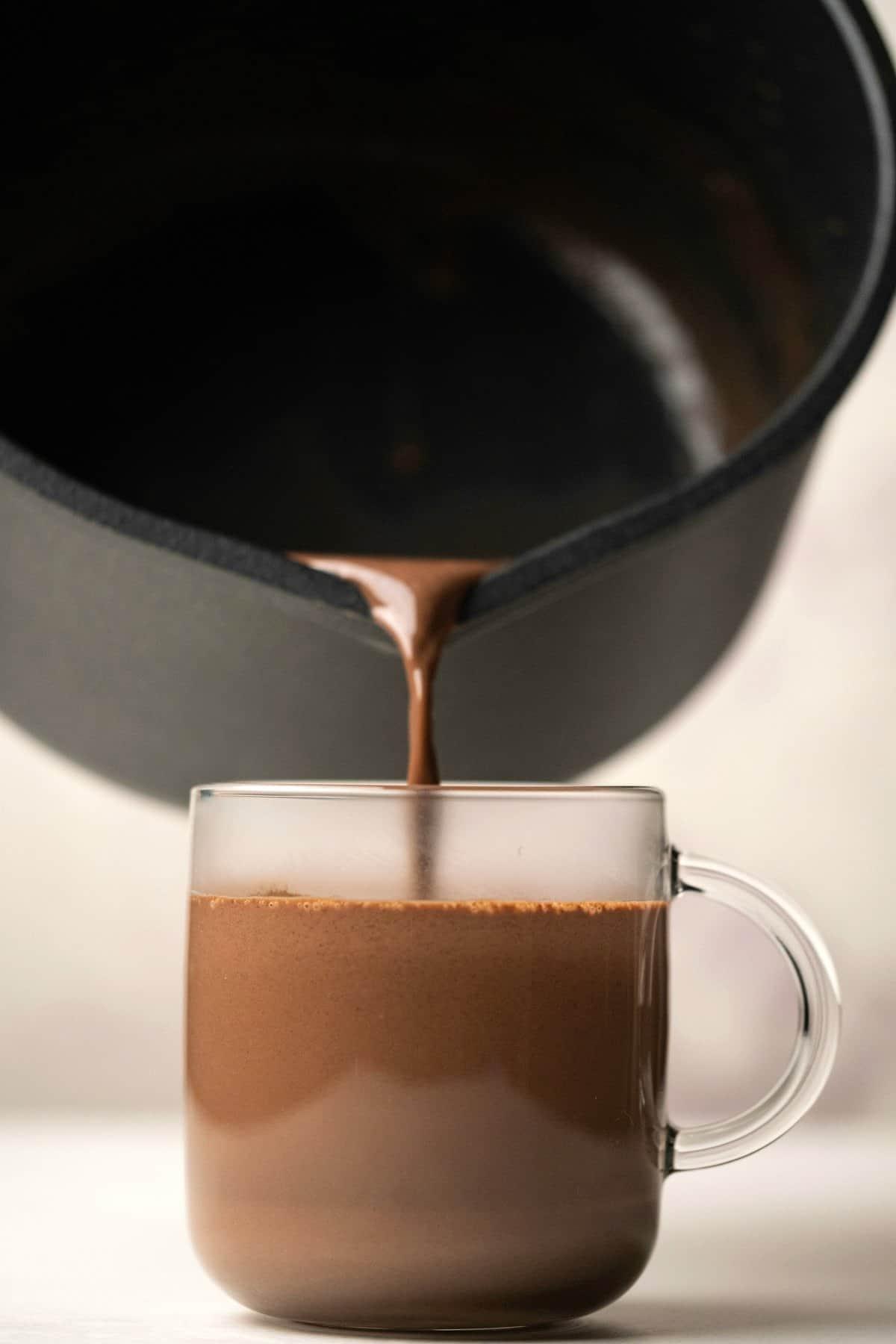Hot chocolate pouring into a glass mug.
