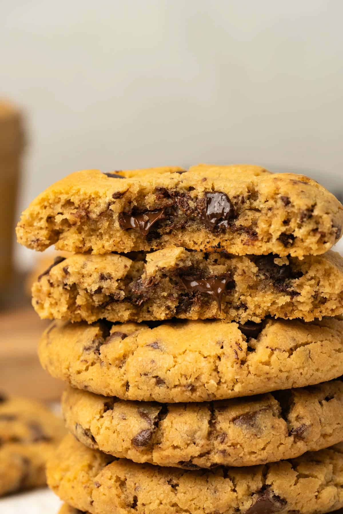 A stack of peanut butter chocolate chip cookies with the top cookie broken in half.