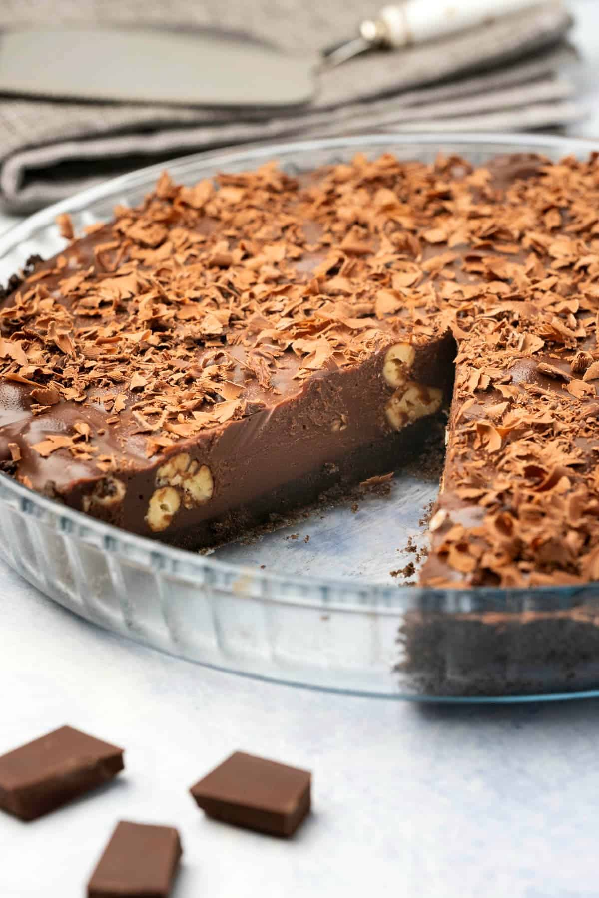 Chocolate Tart topped with chocolate shavings in a glass pie dish.