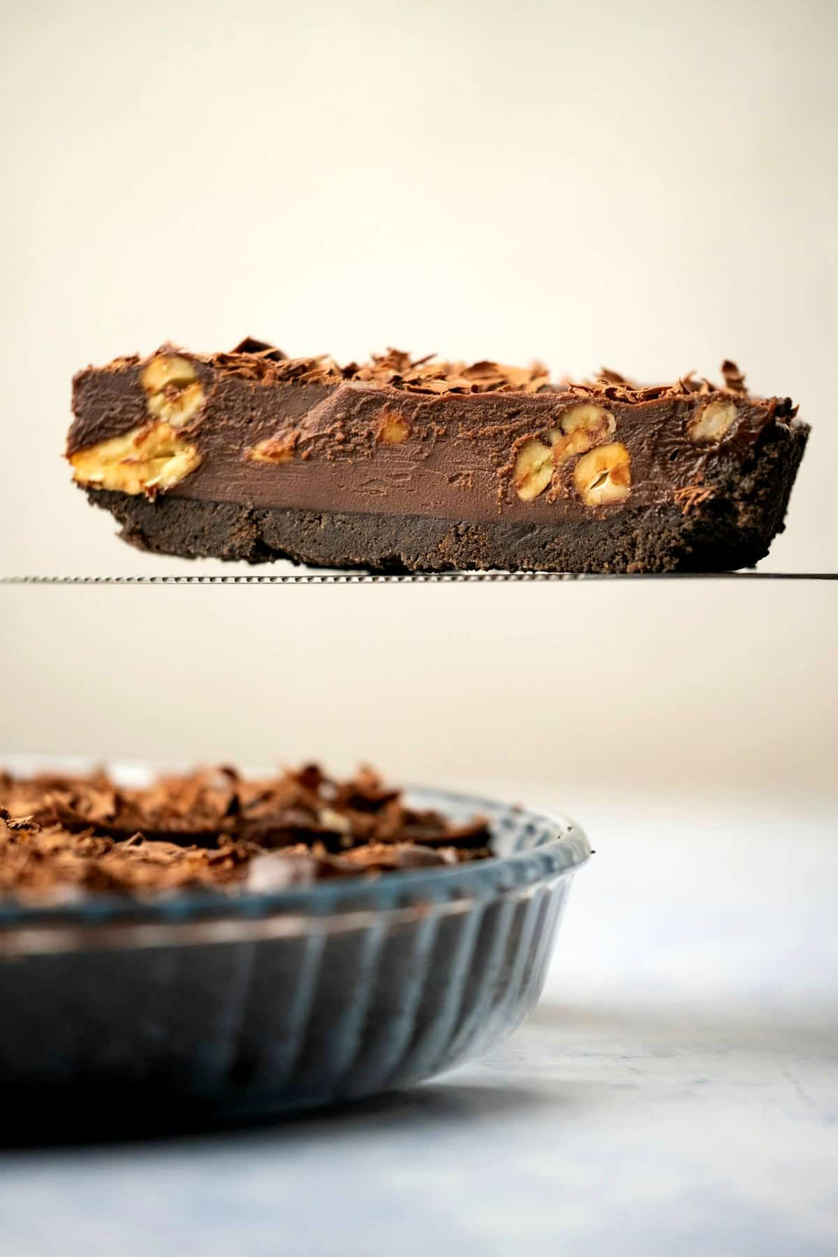 Slice of chocolate tart on a pie lifter.