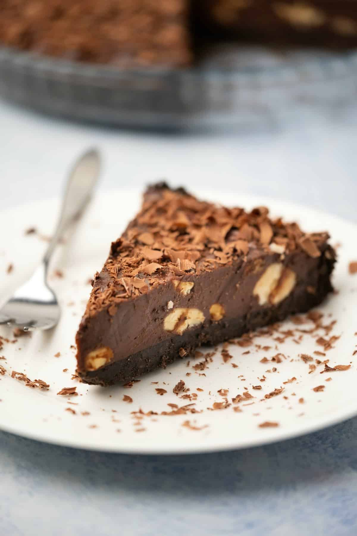 Slice of chocolate tart on a white plate with a cake fork.