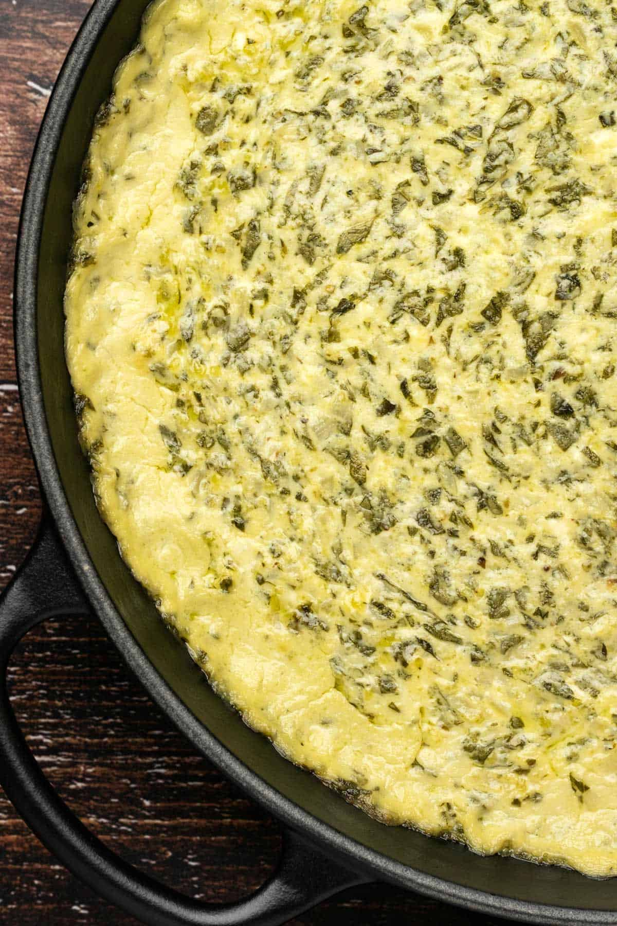 Baked spinach dip in a cast iron skillet.