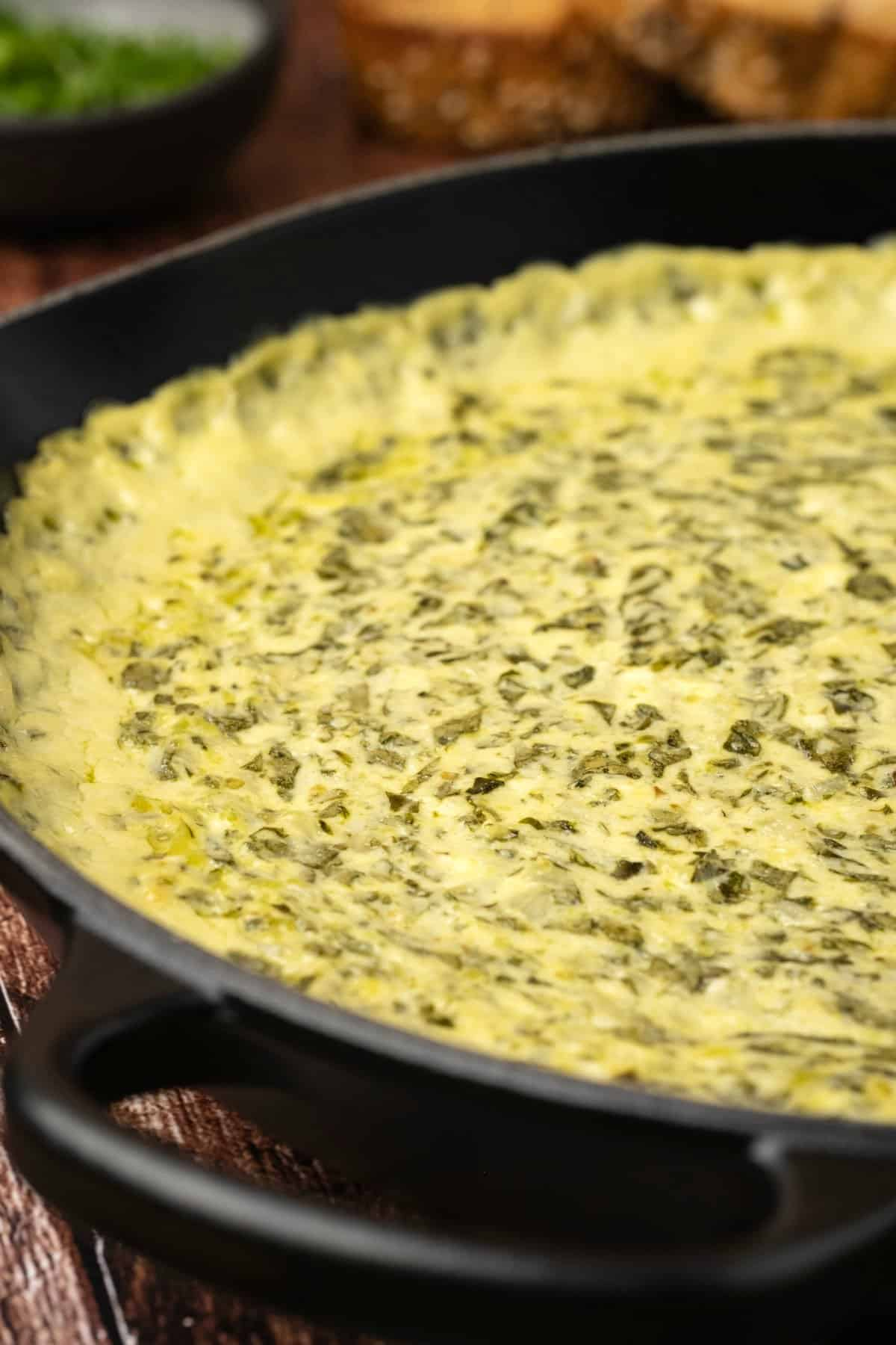 Freshly baked spinach dip in a cast iron skillet.