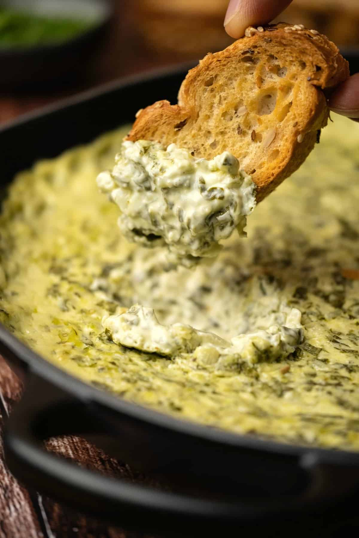 Toasted baguette dipping into baked spinach dip.
