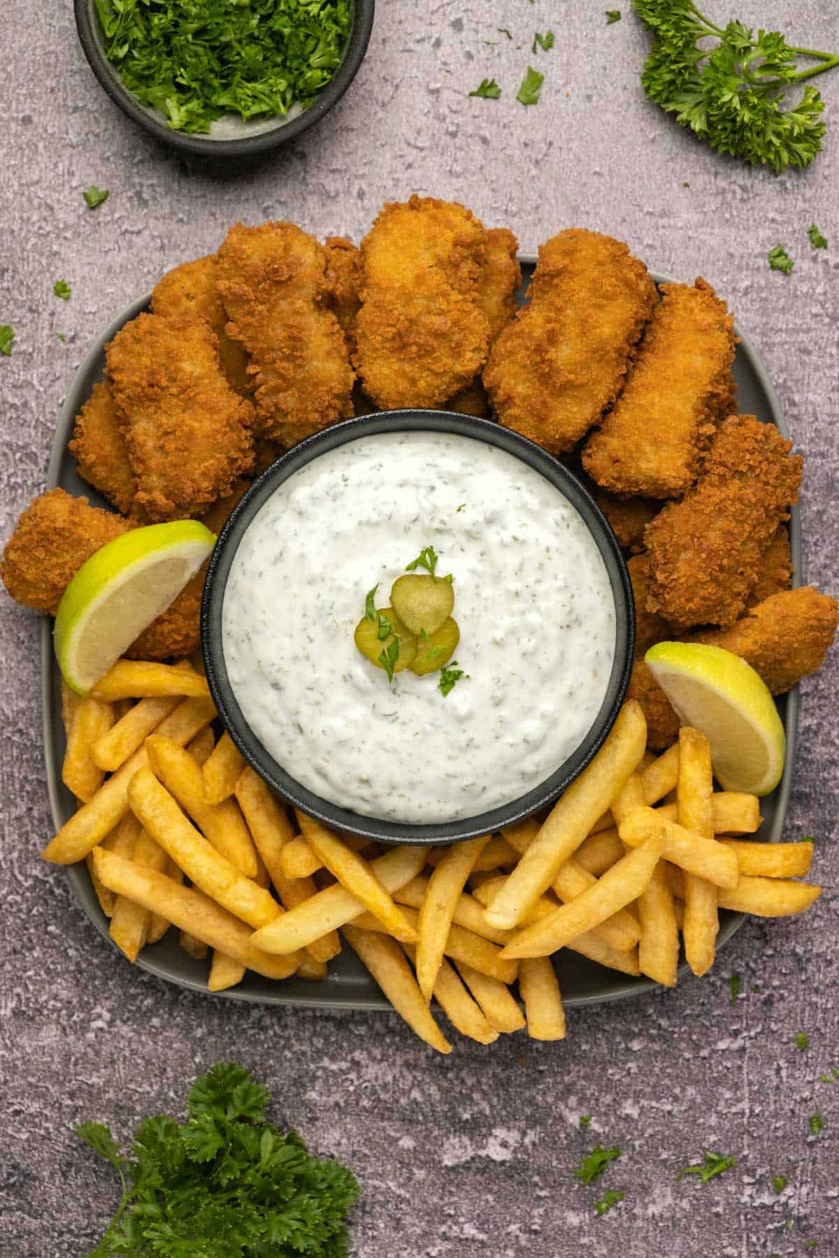 Homemade tartar sauce in a black bowl with fries and nuggets.