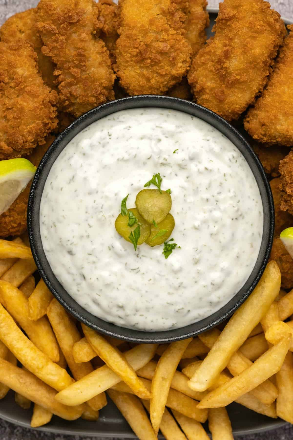 Tartar sauce topped with sliced pickles in a black bowl.