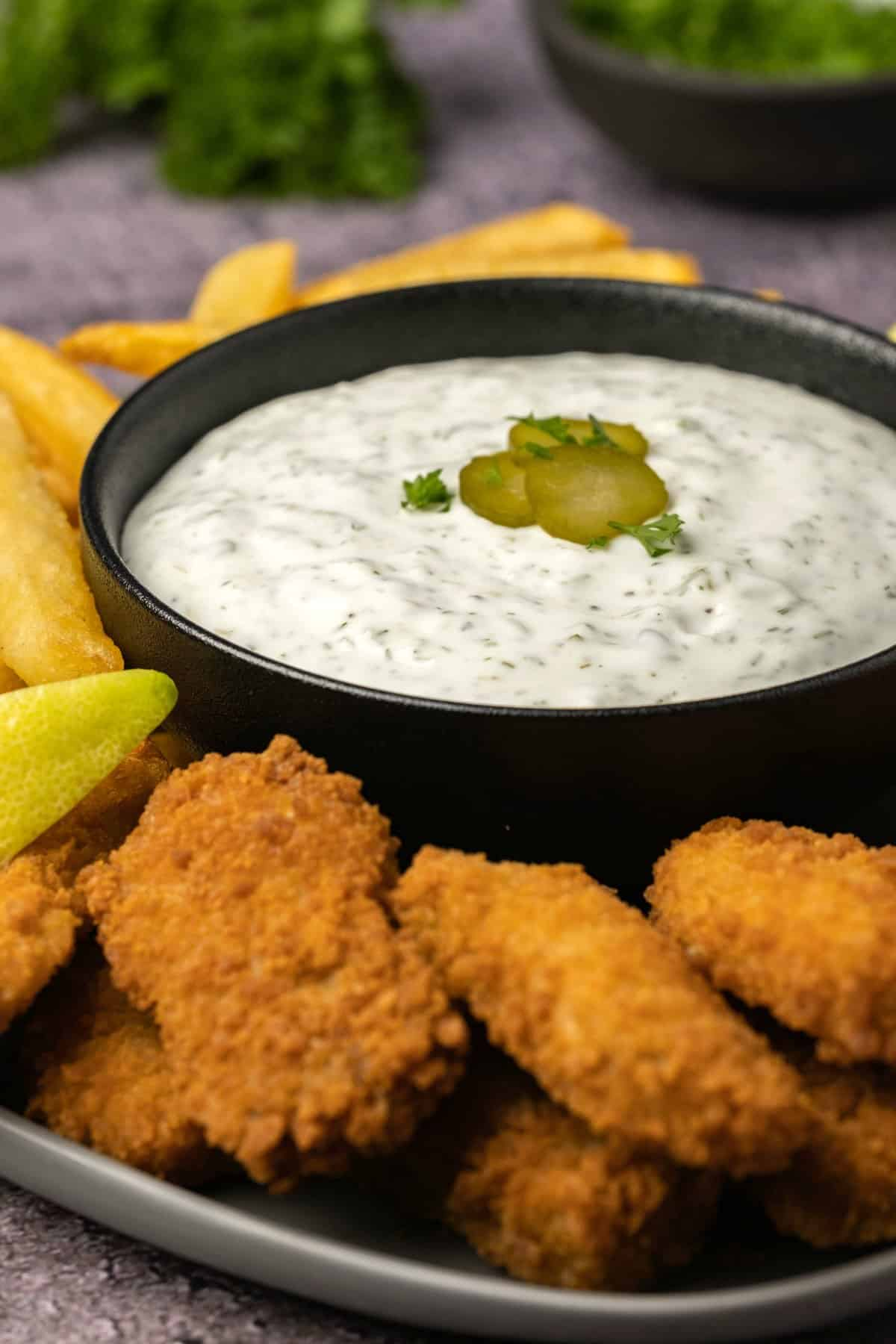 Tartar sauce in a black bowl with nuggets and fries.