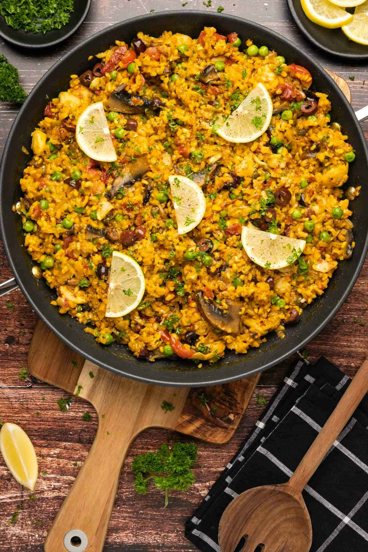 Vegetable paella topped with lemon slices and fresh parsley in a black paella pan.