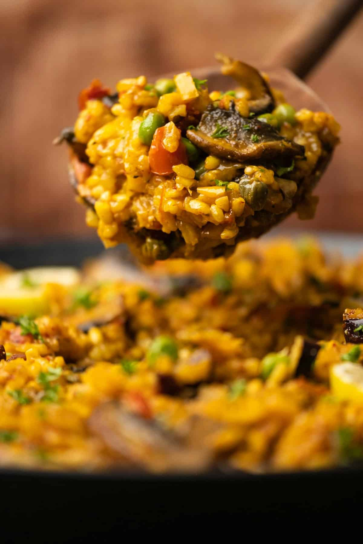 A serving spoon full of vegetable paella.