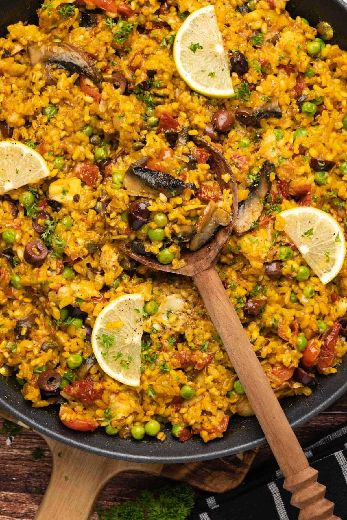 Vegetarian paella in a black paella pan with a wooden serving spoon.