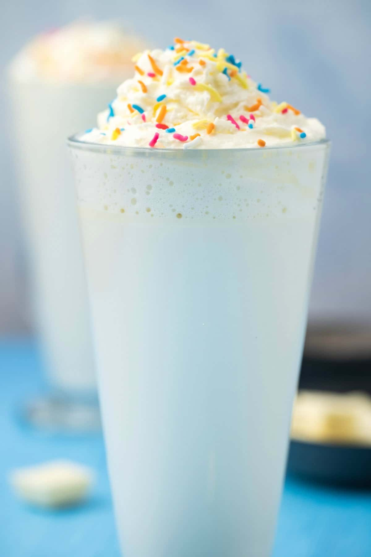 White hot chocolate topped with whipped cream in a tall glass.