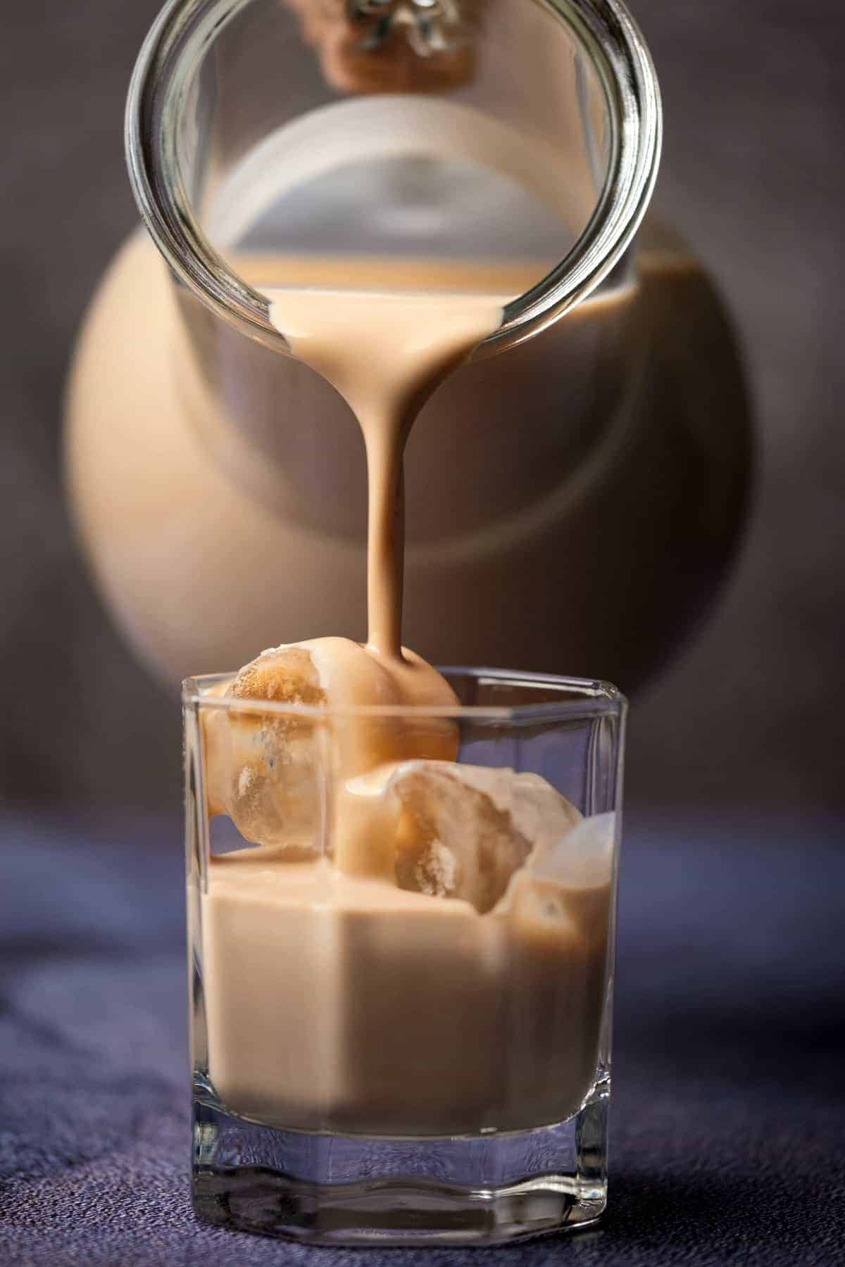 A glass jug pouring homemade Irish Cream into a glass with ice.