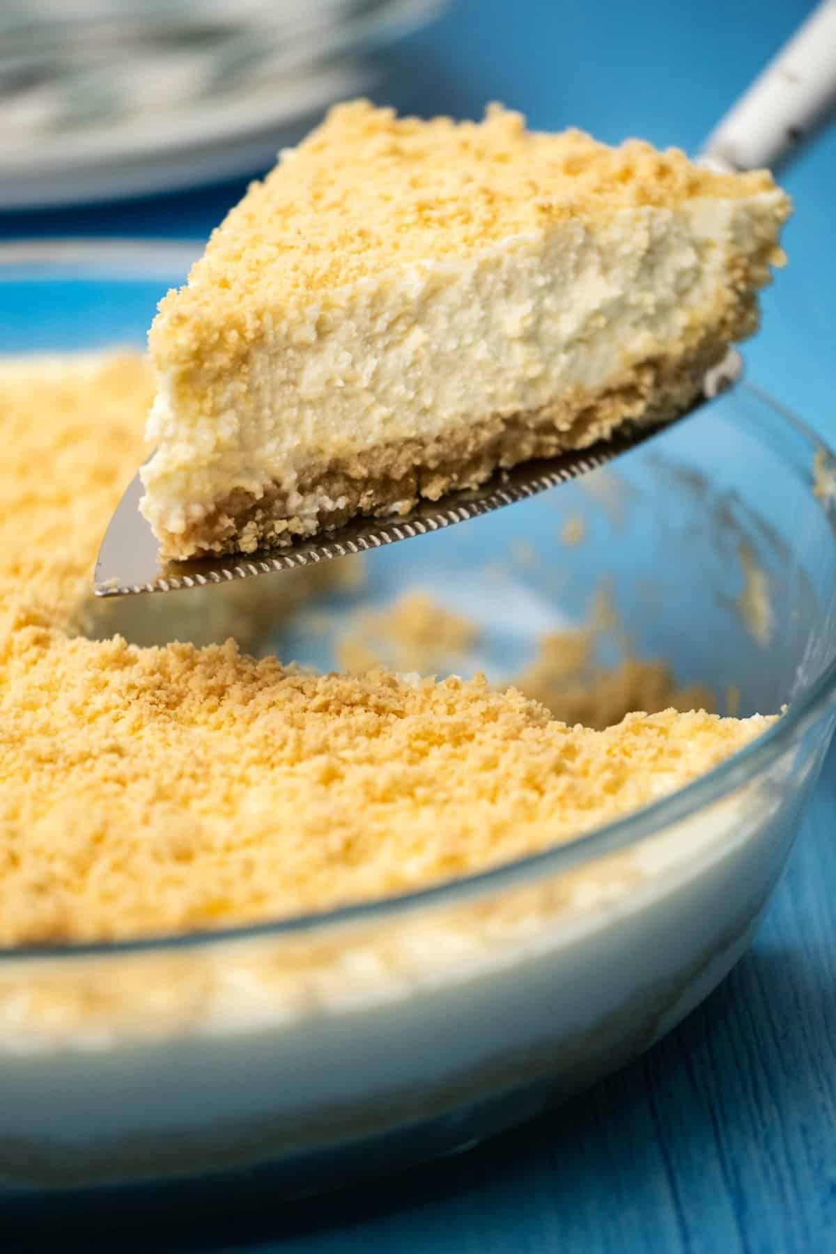 A slice of Greek yogurt cheesecake on a cake lifter.