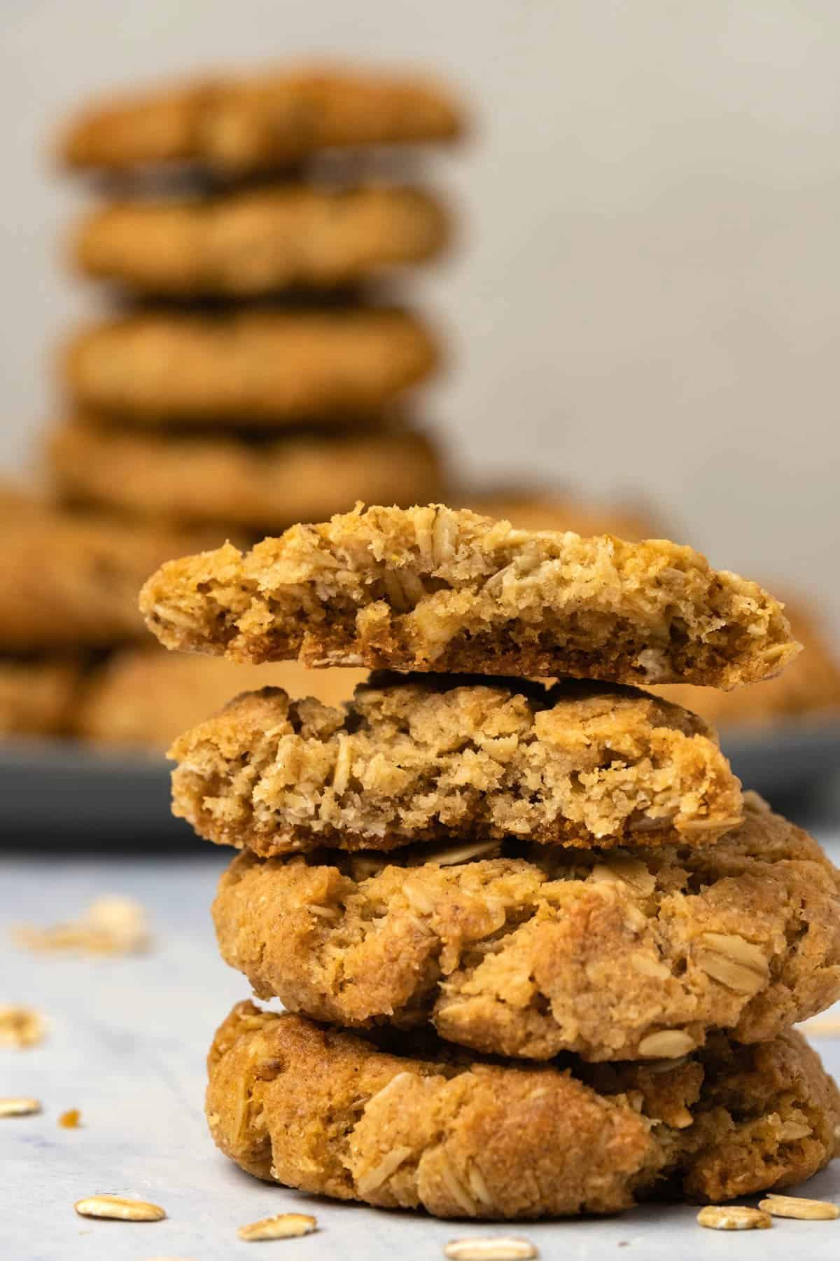Stack of oatmeal cookies with the top cookie broken in half.