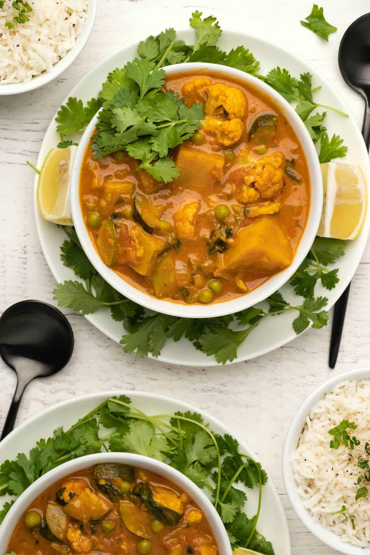 Vegetable curry with fresh cilantro in a white bowl.