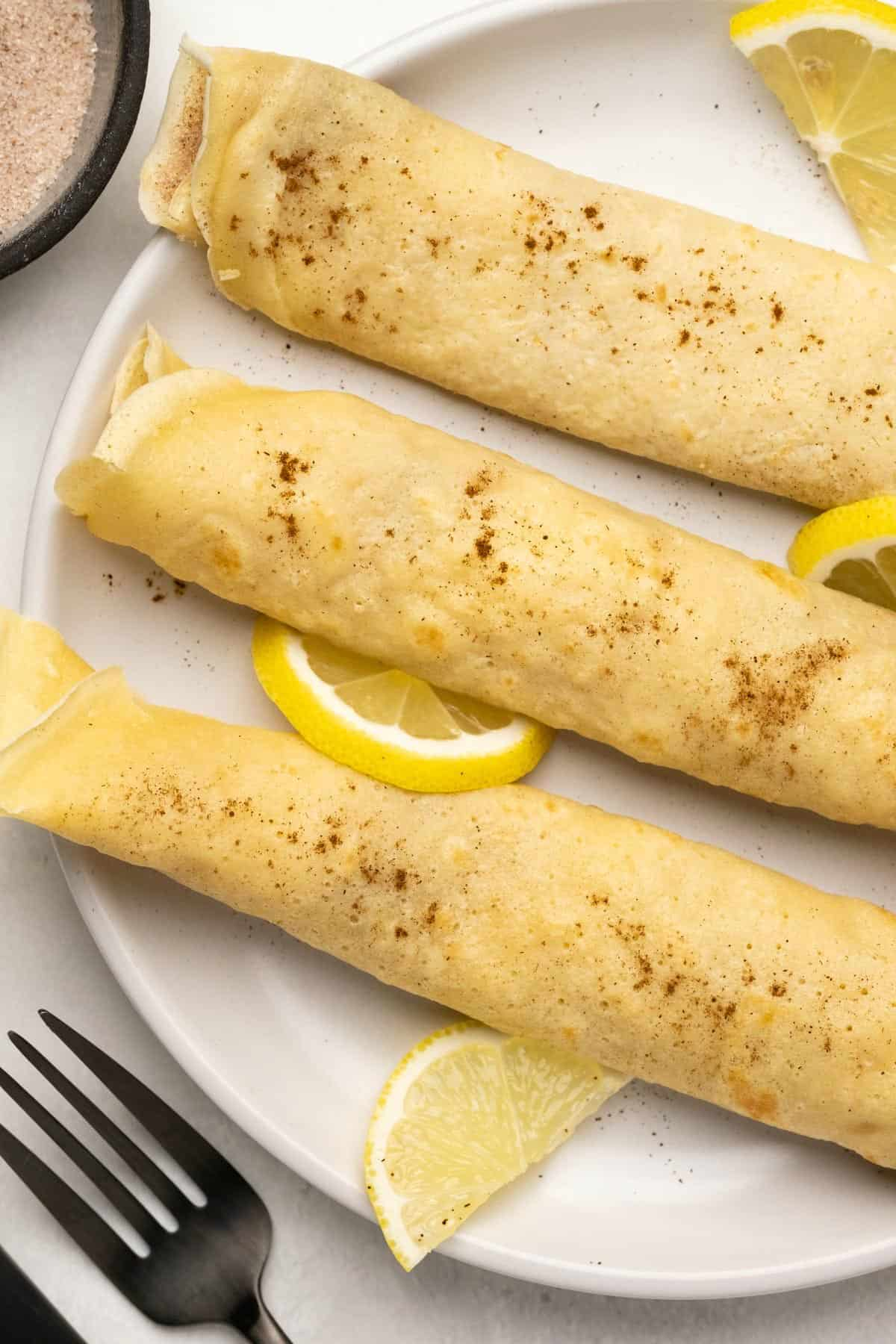 Crepes on a white plate with fresh lemon slices.
