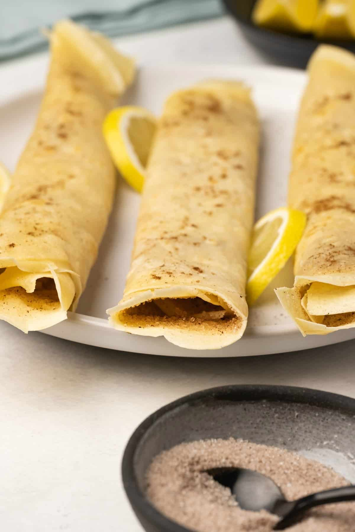 Crepes rolled up on a white plate.