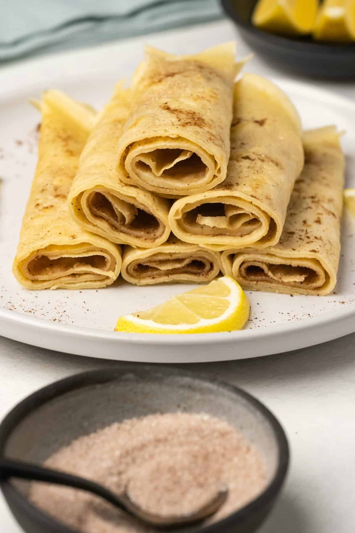 Crepes rolled up and cut in half on a white plate.