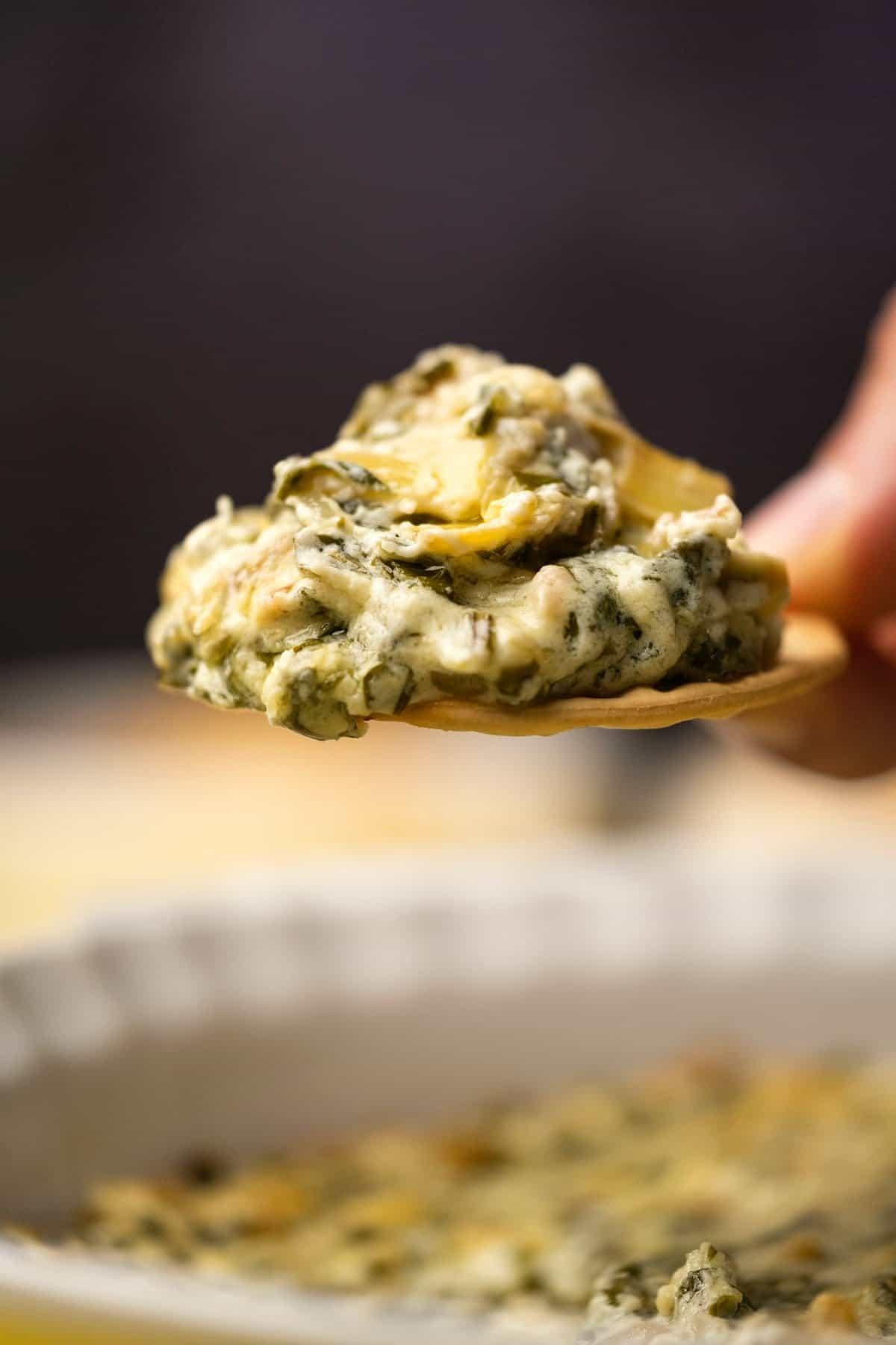 Spinach artichoke dip on a cracker.