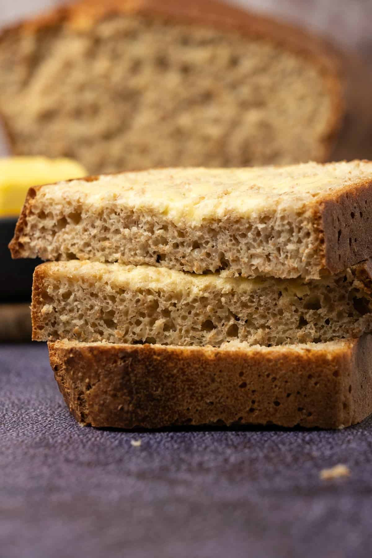 Slices of buttered homemade brown bread in a stack.
