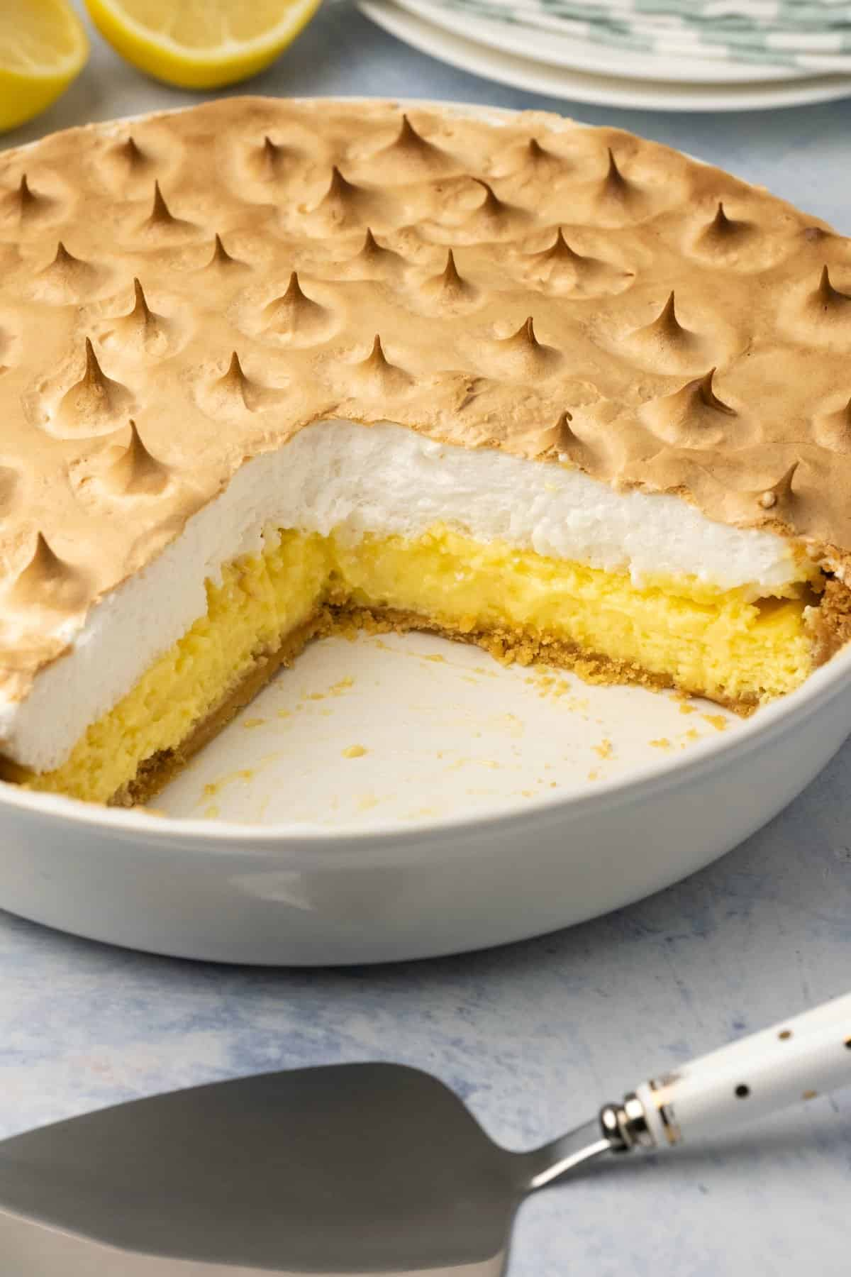 Lemon meringue pie in a white pie dish with a couple of slices removed.